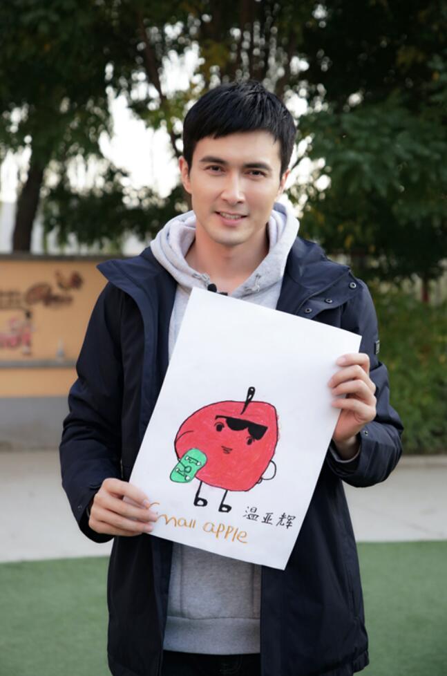 新村民高伟光展示小朋友画的苹果画.JPG